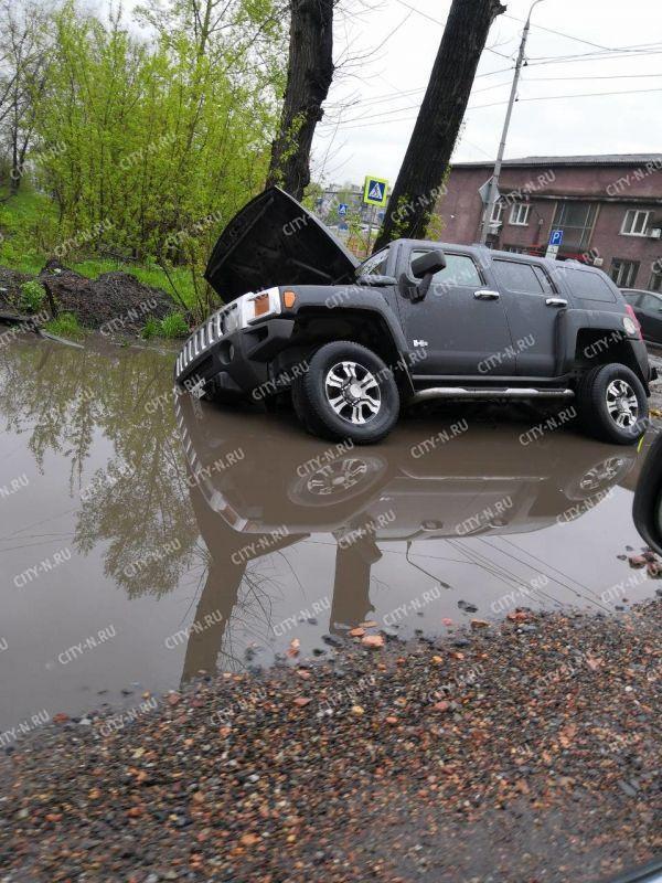 Остерегайтесь луж: в Новокузнецке в ловушку попали внедорожник и трактор
